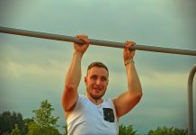 man grimacing on pull up bar